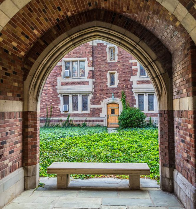 brick and stone archway with a bench at college campus looking out to green quad